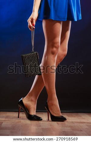 Celebration disco and evening fashion concept - woman in blue dress holding handbag bag, dancing in the club, part of body female legs in high heels on party floor