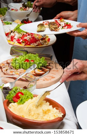 Celebration event with catering table and people hands with plates - stock photo
