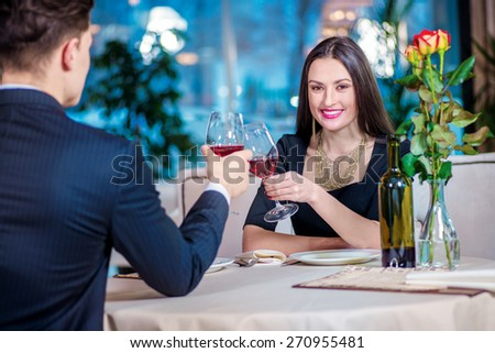 Celebration events at the restaurant. Young couple sitting at a table at each other and smiling lovingly at the restaurant while toasting with wine. - stock photo