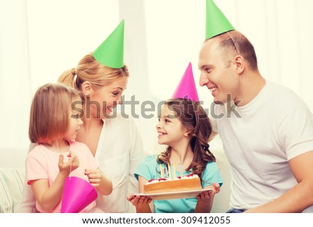celebration, family, holidays and birthday concept - happy family with two kids in hats with cake at home - stock photo