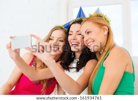 celebration, friends, bachelorette party, birthday concept - three smiling women in blue hats having fun with smartphone photo camera - stock photo
