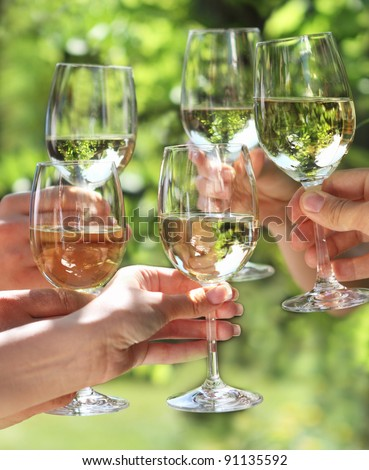 Celebration. People holding glasses of white wine making a toast - stock photo