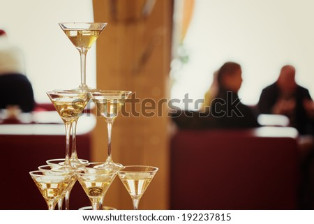 Celebration. Pyramid of champagne glasses. Gently toned. Silhouettes of people on the background. - stock photo