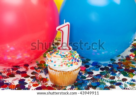 Celebration with balloons, confetti, cupcake, and number 1 candle.