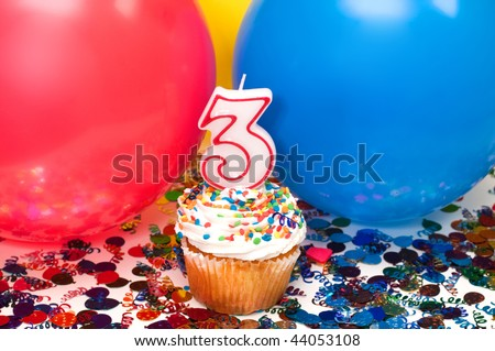 Celebration with balloons, confetti, cupcake, and number 3 candle.