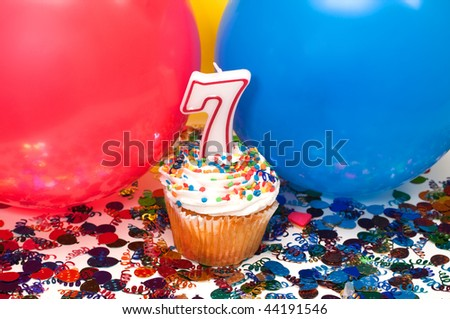 Celebration with balloons, confetti, cupcake, and number 7 candle.