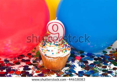Celebration with balloons, confetti, cupcake, and number 9 candle.