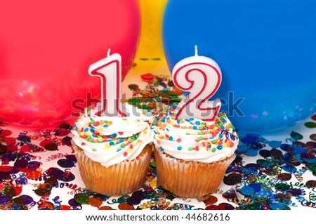 Celebration with balloons, confetti, cupcake, and number 12 candle. - stock photo