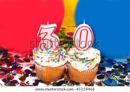 Celebration with balloons, confetti, cupcake, and number 30 candle. - stock photo