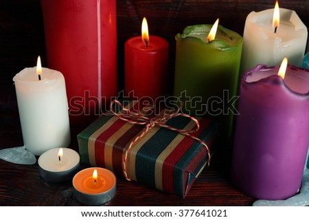 Celebration with of gift box and candles in front of a wooden wall and on a wooden table
