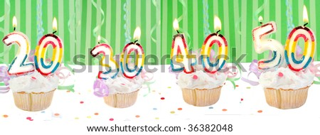 Celebratory birthday cupcakes with lit candles and numbers like twenty, thirty, forty, and fifty with confetti and green striped background - stock photo