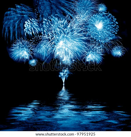 Celebratory blue firework in a night sky - stock photo