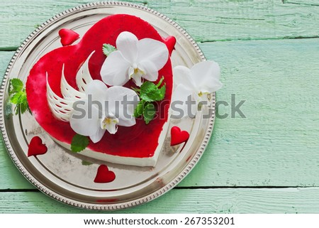 celebratory cake in the form of heart with orchid flowers on a wooden background. valentine's day, mother's day. copy space background - stock photo