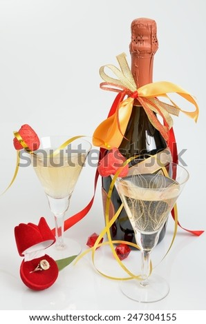 Celebratory still-life with a ring-gift, champagne and wine glasses