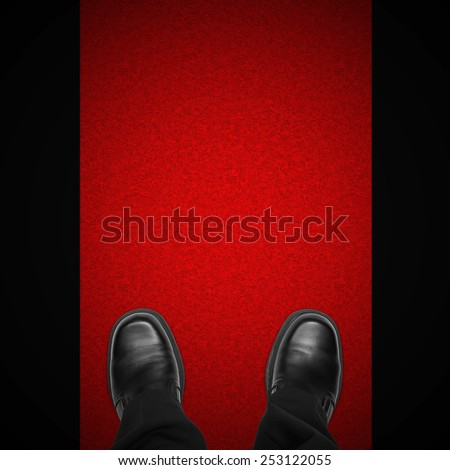 Celebrity man feet on red carpet against black background, overhead view - stock photo