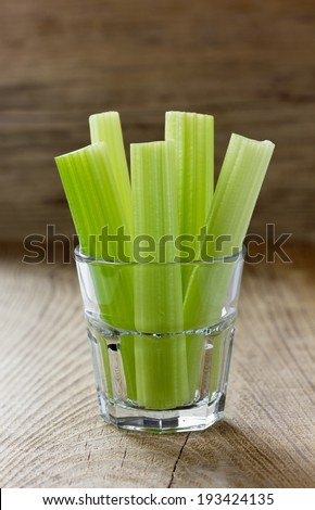 Celery stems on a wooden rustic board, selective focus - stock photo