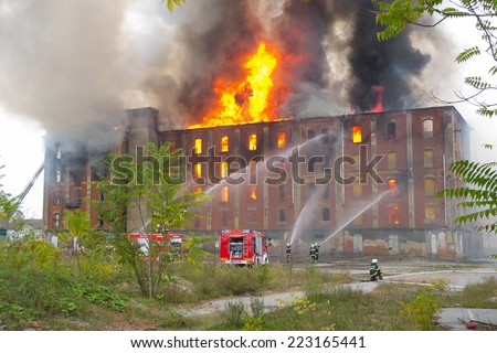 CELJE, SLOVENIA - OCTOBER 06, 2014: Firemen fight large-scale fire of historic industrial building Rakusev Mlin on October 6, 2014 in Celje. - stock photo
