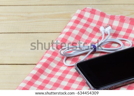 Cell phone and cable on napkin cloth, wooden background