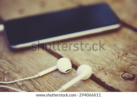 cell phone and headphones lay on an old wooden table - stock photo