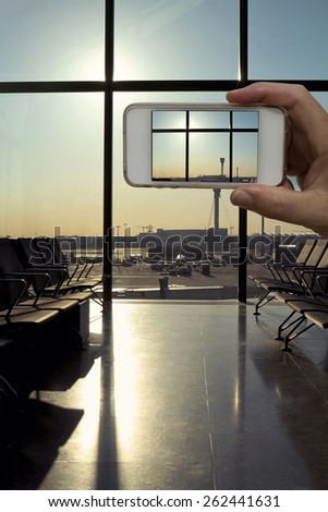 Cell phone camera taking a photo from the departure lounge waiting area at a modern airport - stock photo