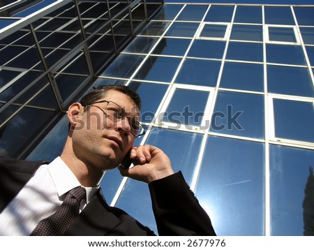 Cell phone communication.Young businessman talking to the cell phone in front of an office  . - stock photo