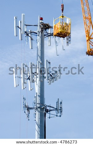 Cell phone company upgrading a communications tower - stock photo