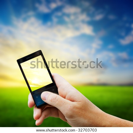 cell phone in hand and country sunset - stock photo