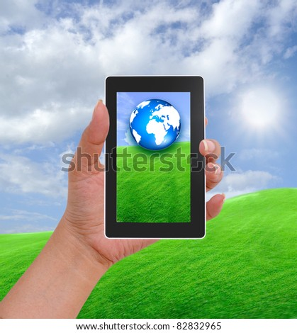 Cell phone in hand and country view of sunny day - stock photo