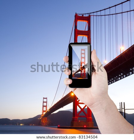Cell phone in hand and golden gate view on sunny day - stock photo