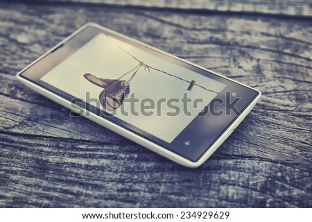 Cell phone on wooden table background - stock photo