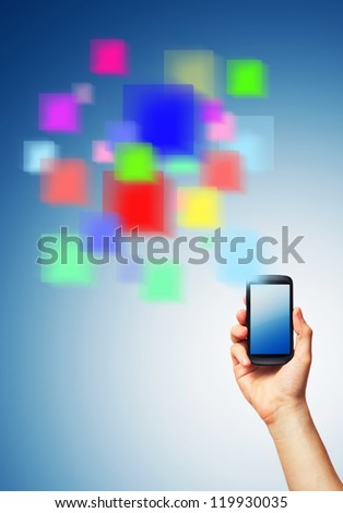 Cell phone (smartphone with touchscreen) in male hand and a futuristic digital depiction of social media over blue background - stock photo