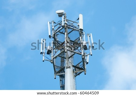 Cell  phone tower rises against a blue sky. - stock photo