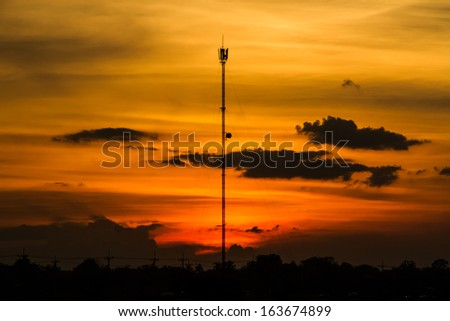 Cell phone tower silhouette with sunset background.