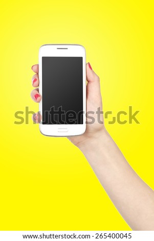 Cell phone with touchscreen in female hand on yellow background - stock photo