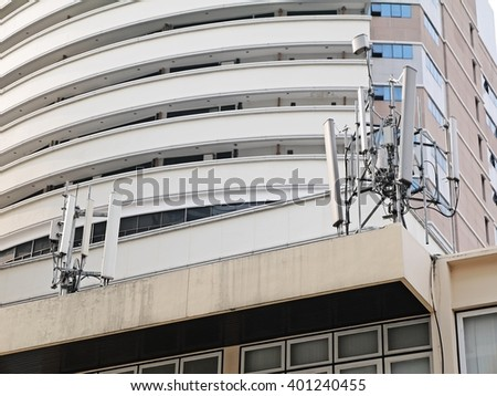 Cell site Post / transmitters on the roof top of white building with office building as background. - stock photo