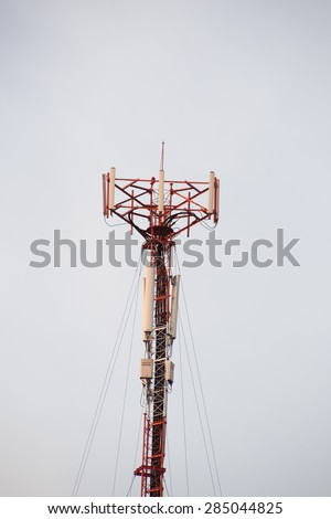 Cell site, Telecommunications radio tower or mobile phone base station with atop the antennas isolated with white sky background. - stock photo