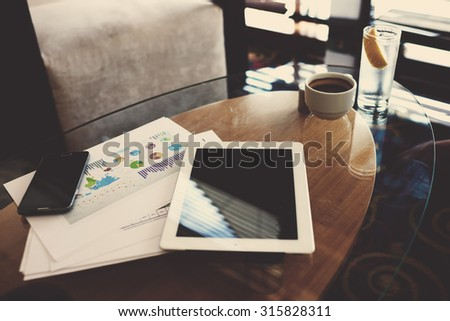 Cell telephone and digital tablet with blank copy space screen for your advertising content or tex message lying on the office table, paper documents with charts and cup of coffee - stock photo