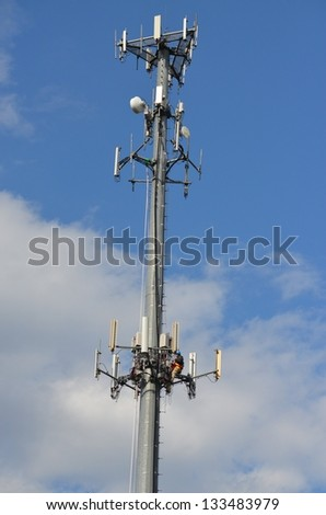 Cell tower against a blue sky with a worker fixing a problem on the pole. - stock photo