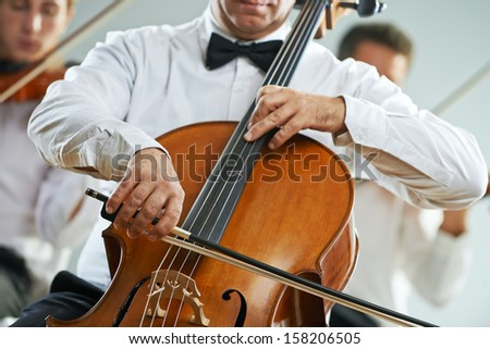 Cellist and violinist playing at the concert - stock photo
