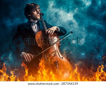 cellist in the fire and smoke - stock photo