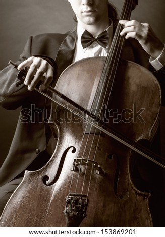 Cellist playing classical music on cello on black background - stock photo