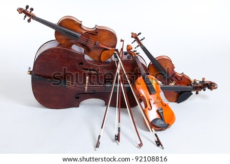 Cello and three violins, all vintage instruments. - stock photo