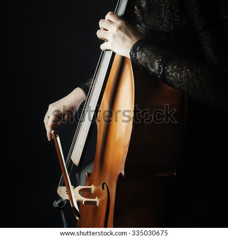 Cello player cellist playing music instrument hands closeup. Orchestra instruments - stock photo
