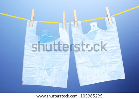 Cellophane bags hanging on rope on blue background - stock photo