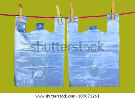 Cellophane bags hanging on rope on green background - stock photo