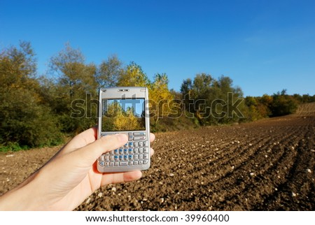 Cellphone in hand and bright autumnal rural landscape