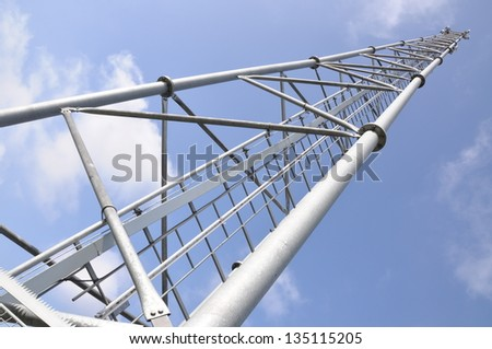 Cellphone mast against blue sky - stock photo