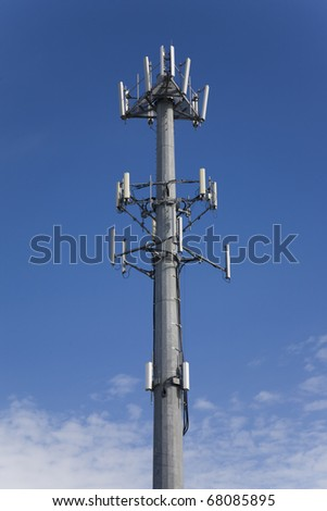 Cellphone tower showing multiple antennas against a blue sky. - stock photo