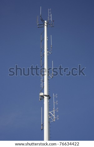 Cellphone tower showing multiple antennas against a blue sky - stock photo