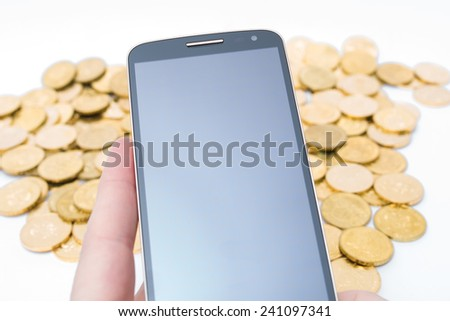 Cellphone with golden coins in the background - stock photo
